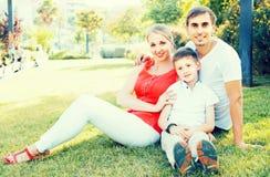 Parent con el muchacho en la edad adolescente que se sienta en hierba verde en parque Imágenes de archivo libres de regalías