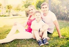 Parent con el muchacho en la edad adolescente que se sienta en hierba verde en parque Fotografía de archivo