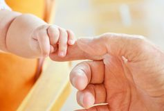 Parent, contact newborn hands with daddy stock photo
