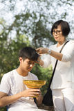 Parent cut hair of their son before buddhist monk ordination cer Royalty Free Stock Photo