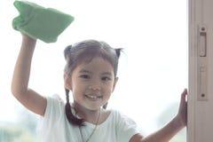 Parent de aide de fille asiatique mignonne de petit enfant pour nettoyer la fenêtre photographie stock libre de droits
