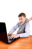 Parent dragging Son from Laptop Stock Images