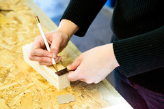 Parent draws stencil on wood block for Pinewood Derby car Stock Image