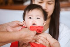 Parent is dresses her asian baby girl with carefully. And love Royalty Free Stock Image