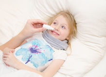 Parent drips drug in the little girl's nose Royalty Free Stock Images