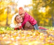 Parent et badinez le mensonge ensemble sur les feuilles en baisse en automne Photo stock