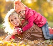 Parent et enfant se trouvant ensemble sur les feuilles en baisse extérieures Photographie stock libre de droits