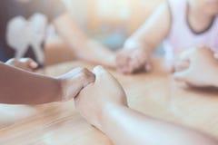 Parent et enfants tenant des mains et priant ensemble Photos stock
