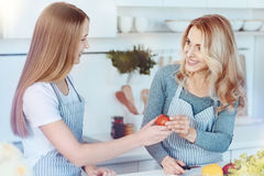 Parent féminin affectueux et fille souriant tout en faisant la salade ensemble Photo libre de droits