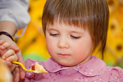 Parent feeding girl Stock Images