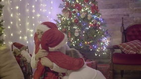 Parent and girl cheering boy wearing santa suit. Having fun and playing together near Christmas tree indoors stock footage