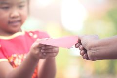 Parent give money in  red envelope to little child girl Royalty Free Stock Photos