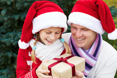 Parent gives the child a Christmas gift Stock Images