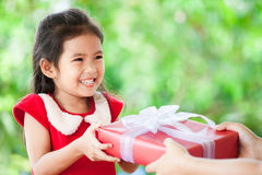 Parent giving Christmas gift to cute asian child girl. On green nature background. Christmas concept Stock Photography