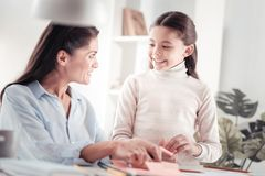 Amicable amusing mother helping her daughter with writing a letter. Parent guidance. Responsible young women poking around paper sheets helping daughter with royalty free stock photography