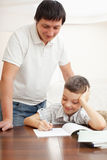 Parent helps his child do homework stock photography