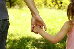 The parent holding the hand of a small child Stock Photography
