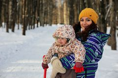Parent holding kid on hands in winter park. Parent holding kid on the hands in winter park Stock Image