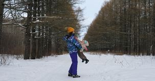 Parent holding kid on hands in winter park. Parent holding kid on the hands in winter park Royalty Free Stock Image