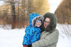 Parent holding kid on hands in winter park. Parent holding kid on the hands in winter park Royalty Free Stock Photo