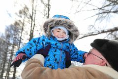 Parent holding kid on hands in winter park. Parent holding kid on the hands in winter park Royalty Free Stock Photography