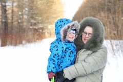 Parent holding kid on hands in winter park. Parent holding kid on the hands in winter park Stock Photo