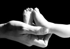 A parent holding a newborn baby's feet. In black and white royalty free stock photography