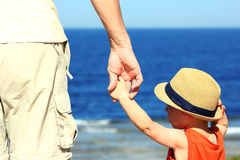 Parent holds the child`s hand on the sea Stock Photos