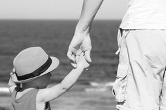 Parent holds the child`s hand on the sea Stock Image
