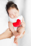 Parent holds/cradles a cute adorable child sleeping in protective arms, cuddling with a red heart stuffy. Chubby 1 yo asian baby sleeping in arms Stock Image