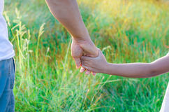 parent holds the hand of a little girl Stock Images