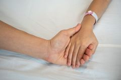 Parent holds the hand of a sick child in a hospital. Mother hand care about her kid Royalty Free Stock Image