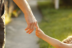 Parent holds the hand of a small child Stock Images
