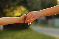 Parent holds the hand of a small child Stock Photos
