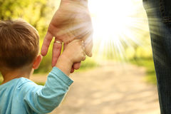 Parent holds the hand of a small child Stock Image
