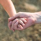 Parent holds the hand of a small child. Father holds the child by the hand. close-up. In the background. Support on the way. stock photography