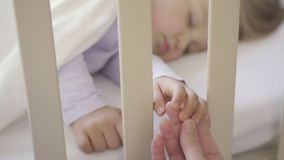 The parent holds the hand of a small child sleeping in a baby crib. Happy family and her newborn baby together. The