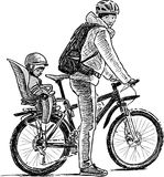Parent with the kid on the bicycle Stock Images