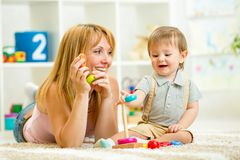 Parent and kid boy playing together indoor. S Stock Photos