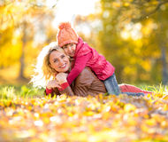 Parent and kid lying together on falling leaves in autumn Stock Photo