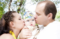 Parent kissing their baby boy. Two parent kissing their baby boy, summer in park Stock Photo