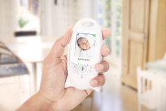 Parent monitoring baby through baby monitor Stock Images