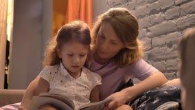 Parent o livro de leitura à menina, à mamã e à criança sentando-se junto no sofá na sala de visitas moderna, conceito de família, filme