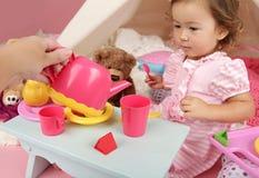 Parent ou ami jouant avec des enfants à la maison : Thé d'enfant en bas âge Image stock