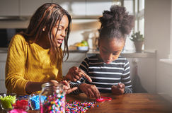Parent pointing at beads with girl at table Royalty Free Stock Photos