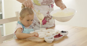 Parent pouring muffin batter into holders Royalty Free Stock Photo