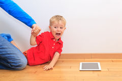 Parent pulling child from touch pad Stock Photo