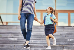 Parent and pupil go to school. Parent and pupil of primary school go hand in hand. Woman and girl with backpack behind the back. Beginning of lessons. First day Stock Photo