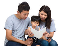 Parent reading book with baby son Stock Photo