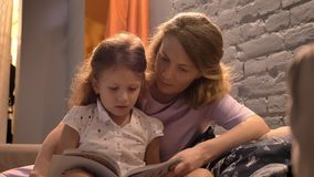 Parent reading book to little girl, mom and kid sitting together on sofa at modern living room, family concept, indoors stock footage